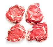 Four rib-eye steaks. Four raw rib-eye beaf steaks isolated on white background Royalty Free Stock Photos