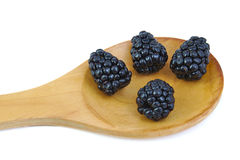 Four ripe blackberries in a wooden spoon. Stock Image