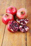 Four ripe pomegranate fruit on wooden surface. One cut open Stock Photography