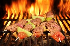 Four Roasted Beef Kebabs With Vegetables On BBQ Flaming Grill Stock Photo