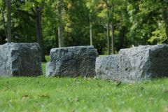 Four rocks in the grass in the park royalty free stock photos