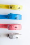 Four rolls of colorful measuring tapes Stock Images