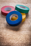 Four rolls of insulating tape on wooden board Stock Photo