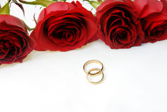 Four roses and two wedding rings Royalty Free Stock Images