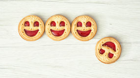Four round biscuits smiling faces, one of them falls down Royalty Free Stock Photo