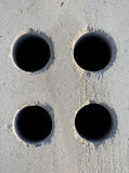 Four round holes in grey concrete wall. Stock Photos