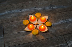 Four round orange candle burning in the stands of the orange pee Royalty Free Stock Image
