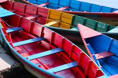Four Rowboats Resting on a Lake in Nepal. Four hand-painted rowboats on a lake in Nepal, very bright colors, clean design Stock Photography