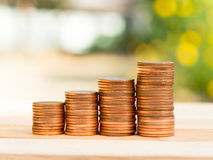 Four rows of rising growth golden stack coins with green nature background. Growing and saving money concept.  Royalty Free Stock Images