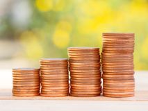 Four rows of rising growth golden stack coins with green nature background. Growing and saving money concept.  stock images