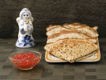 Four ruddy pancake neatly on the plate bowl with red caviar. Next figure of an angel holding a Church candle royalty free stock photo