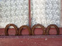 Four horseshoes in an old window with curtain. Four rusty horseshoes placed in a row in an old window with rustic curtain background Stock Photos