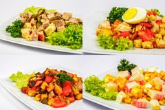Four salads for christmas table. Four salads with meat, tomatoes crab sticks, crackers, cucumbers, corn and egg on white plate for celebration table Stock Photo