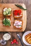 Four sandwiches with fresh vegetables, tomatoes, cucumbers, radish and arugula on a wooden background. Homemade butter Stock Image