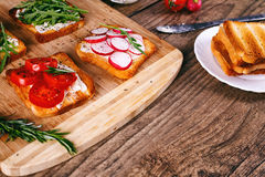 Four sandwiches with fresh vegetables, tomatoes, cucumbers, radish and arugula on a wooden background. Homemade butter Stock Images