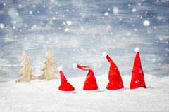 Four Santa Christmas hats in front of snow stars and trees Stock Photo