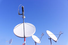 Four satellite antenna. Isolated on a blue sky background Royalty Free Stock Photos