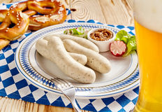 Four sausages with dipping sauce, pretzel and beer Royalty Free Stock Photography