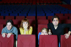 Four scared friends see movie in cinema theater Stock Photography