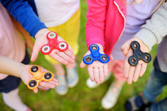 Four school children playing with fidget spinners on the playground. Popular stress-relieving toy for school kids and adults. Royalty Free Stock Images