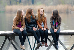 Four school girls sitting on river bridge. Four happy school girls sitting on river bridge on autumn day and looking away Royalty Free Stock Photos