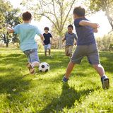 Four schoolboys playing football in the park, square format stock image