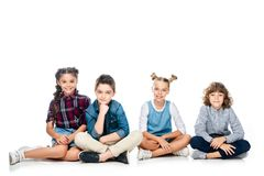 four schoolchildren sitting and looking at camera stock photo