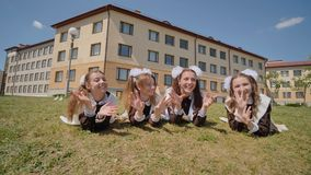 Four schoolgirl graduates are lying on the grass against the backdrop of their school. Girls waving their hands and. Fleeing. Russian school stock video