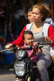 Four on a scooter. THONG PHA PHUM, THAILAND, JANUARY 23, 2016 : Three adults and a child are riding a scooter without helmet protection in the street of Thong Stock Image