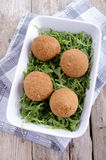Four scotch eggs and wild rocket. In a white bowl Stock Photos