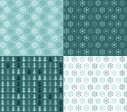 Four seamless Christmas patterns with snowflakes and trees Royalty Free Stock Images