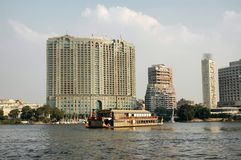 The Four Seasons Hotel Cairo seen from the Nile with a tour boat passing in front. CAIRO, EGYPT - OCTOBER 20, 2008: The Four Seasons Hotel seen from the Nile stock images