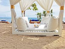 Four Seat Seaside Cabana. No one has yet arrived at this cabana. White curtains, pillows and towels laid out on a white deck. Blue sea and sky with white clouds stock images