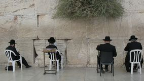Four seated men praying at the wailing wall in jerusalem. Four seated jewish men pray at the wailing wall in jerusalem, israel stock footage