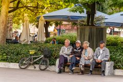 Four senior men sitting in the Central Square, Larissa. Larissa, Thessaly, Greece - May 4th, 2018: Four senior men sitting in a bank placed in the Kentriki stock image
