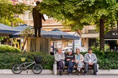 Four senior men sitting in the Central Square, Larissa. Larissa, Thessaly, Greece - May 4th, 2018: Four senior men sitting in a bank placed in the Kentriki stock images
