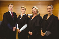 Four serious judges standing while wearing robes Royalty Free Stock Photography