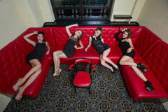 Four sexy girls on a red couch. in the interior Royalty Free Stock Photo