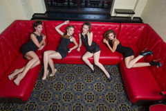 Four sexy girls on a red couch. in the interior Royalty Free Stock Photos