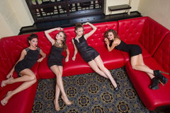 Four sexy girls on a red couch. in the interior Stock Photos