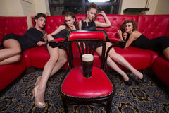 Four sexy girls on a red couch. in the interior Stock Images
