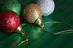 Four Shiny Christmas Balls. Resting on green wrapping paper Royalty Free Stock Photo