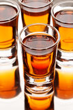 Four shots with alcohol on the reflecting surface. Vertical, selective focus Stock Photo