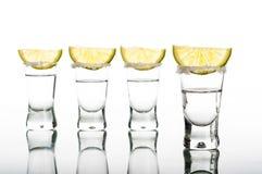 Four shots of vodka with lemon Stock Photos