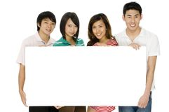 Four With Sign. Four young asian men and women holding a blank sign on white background stock photos