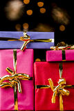 Four Single-Colored Gifts with Golden Bows. Tightly framed shot of four wrapped presents with golden ribbons. Flattened spatial feeling with blurred twinkles in Royalty Free Stock Photos