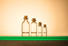Four size of glass bottles  on yellow background Stock Images