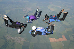 Four skydivers in freefall. High up in the air Stock Photos