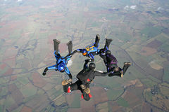 Four skydivers in freefall. On a sunny day Stock Photo