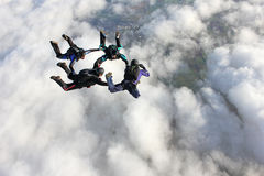 Four skydivers in freefall. Over a bank of clouds Stock Images